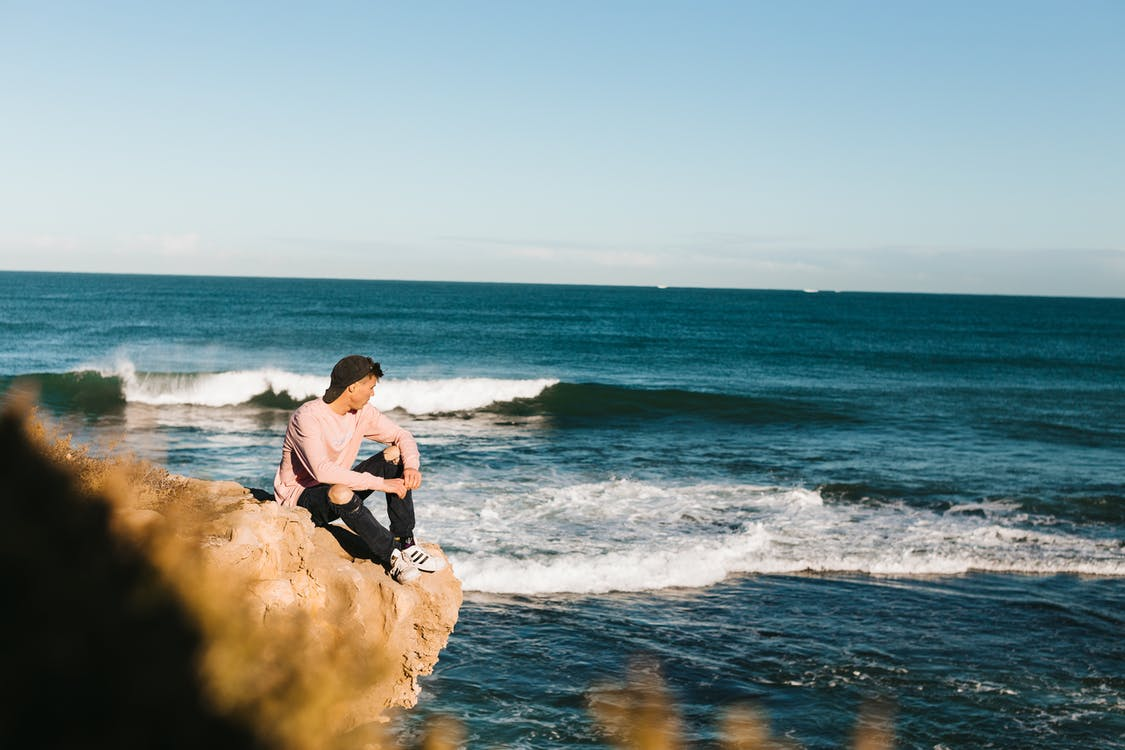 Side view of full body man in casual clothes and sneakers sitting on rocky shore near waving ocean and looking away