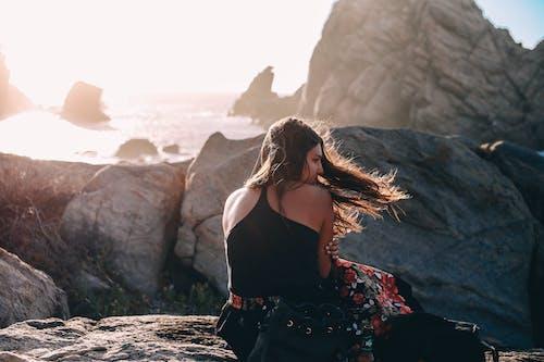 Calm woman on rocky seashore on windy day