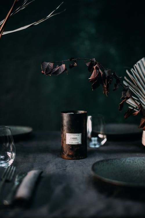 Elegant composition of served table with dark plates and tablecloth near candle in glass and dry twigs in vase with black wall on background