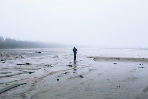 Unrecognizable man walking on humid sandy shore