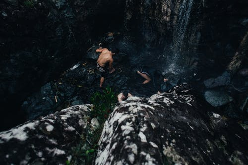 Anonymous tourists climbing cliff