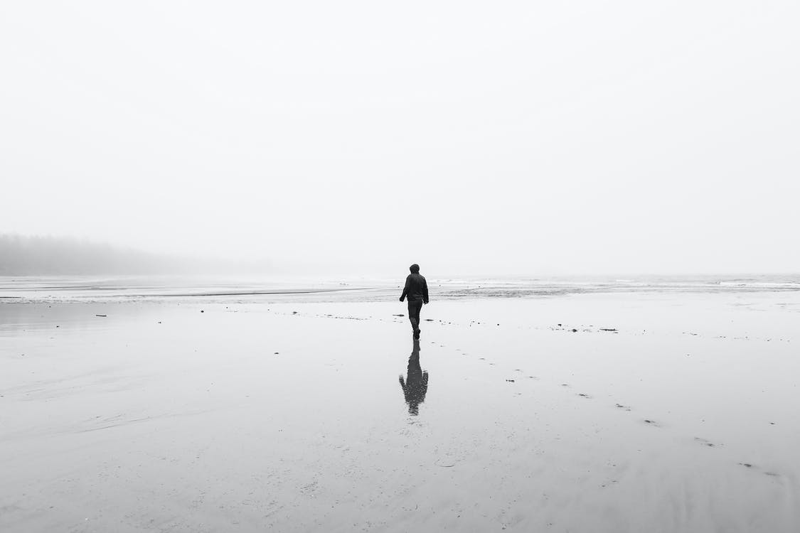 Monochrome back view of full body unrecognizable person in autumn clothes walking on lonely wet sandy coast in overcast day