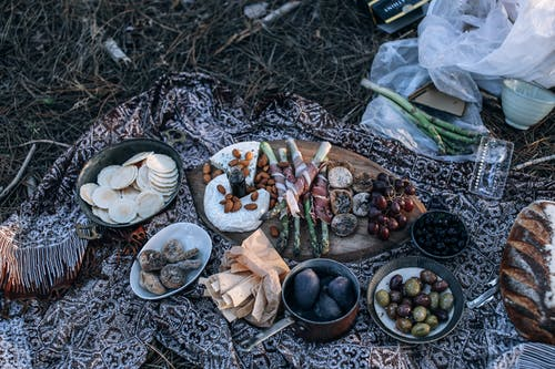 From above of appetizing homemade bread and cheese placed near fruits and vegetables in bowls and on wooden cutting board for picnic on nature