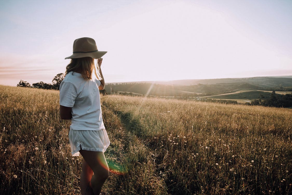 Side view of anonymous woman in white summer outfit and hat standing in field on sunny day