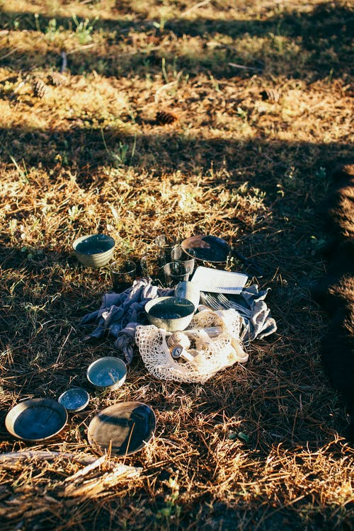 From above of ceramic plates and bowls near knitted bag placed on dry grass in sunbeams