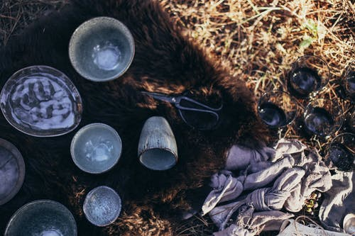 Overhead of composition with ceramic and glass utensil near scissors placed on fur on dry grass on sunny day