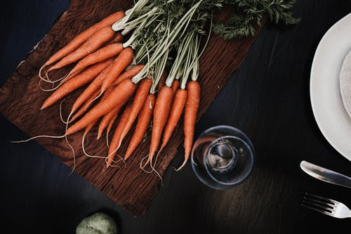 Top view of ripe carrots placed on timber board near glass and plate with knife and fork