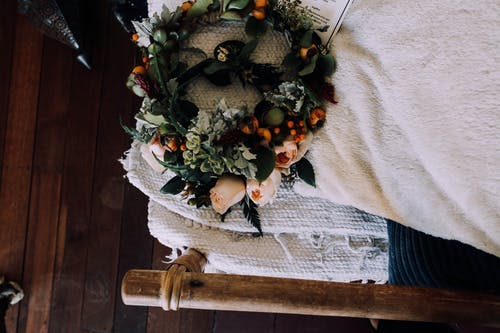 Top view of fresh wreath with delicate roses and verdant leaves placed on timber bed