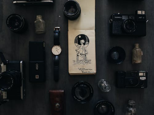 Vintage notebook among photo cameras with lenses