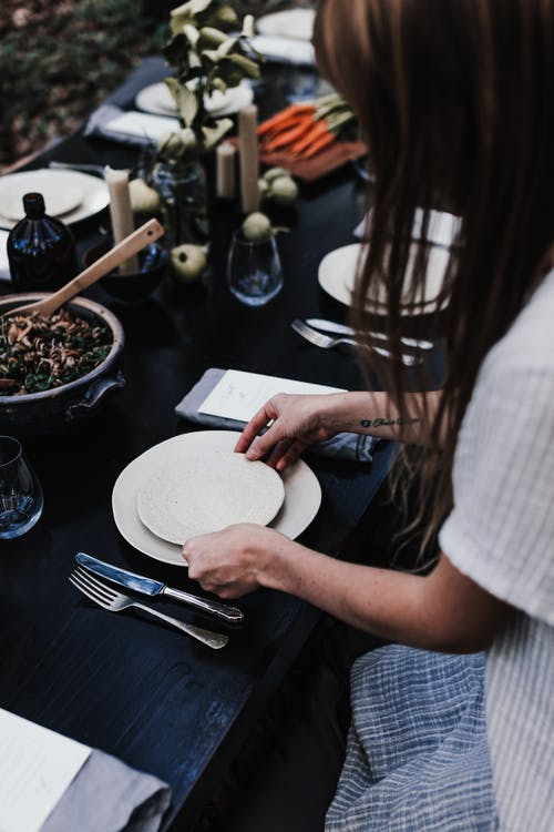 Woman serving plates on table for dinner