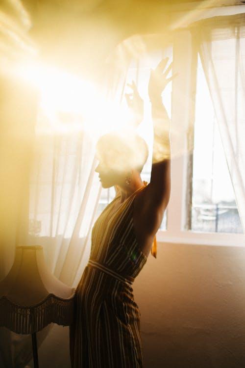 Slender woman dancing near window in bright sunshine