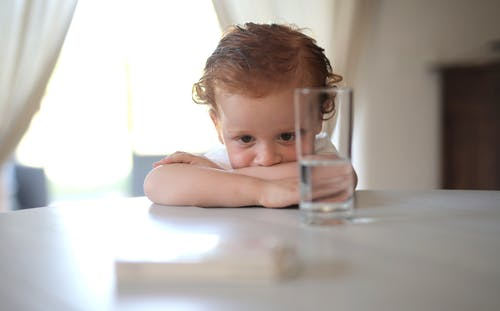 Baby in White Tank Top Holding Clear Glass Mug