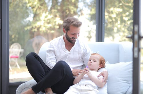 Man in White Dress Shirt and Black Pants Sitting on White Couch Carrying Baby