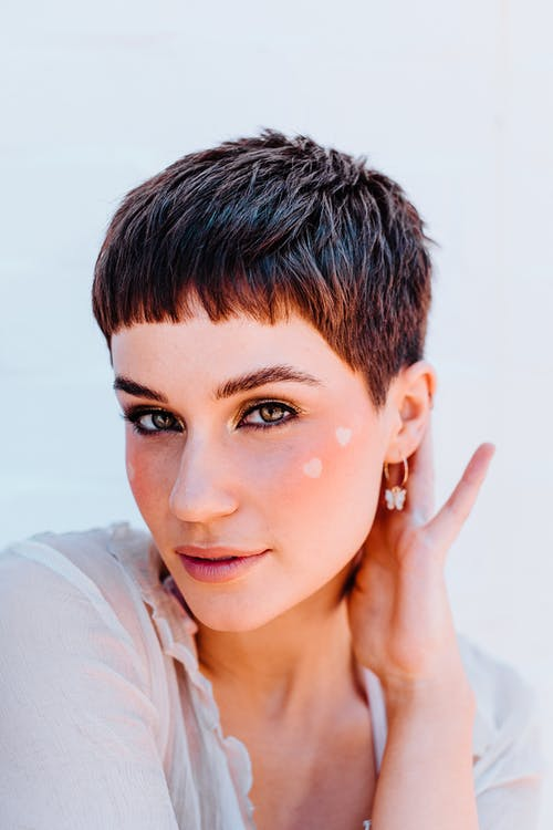 Stylish woman with short hair touching neck