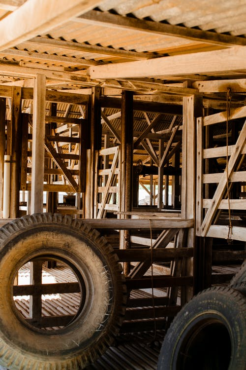 Various rubber tires stacked in aged wooden barn in countryside on sunny day