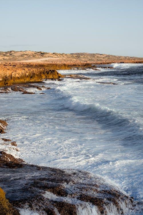 Stormy sea waving near rocky shore on sunny day