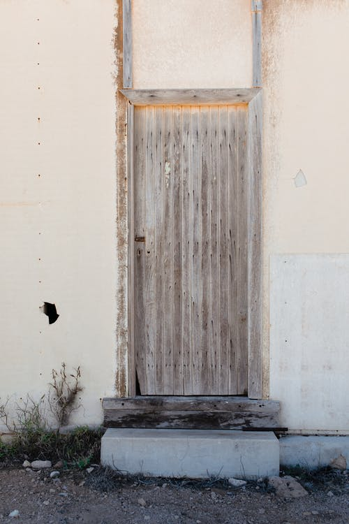 Old wooden door of shabby white house in countryside