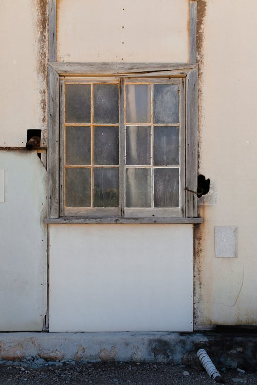Old wooden window on white wall of shabby rustic house located in suburban district on sunny day