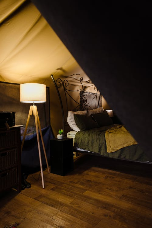 Comfortable forged bed with nightstand and lamp placed in cozy tent house at campsite