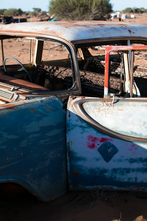 Fragment of old damaged automobile covered with rust with open door and peeling paint placed on ground in sunny junkyard