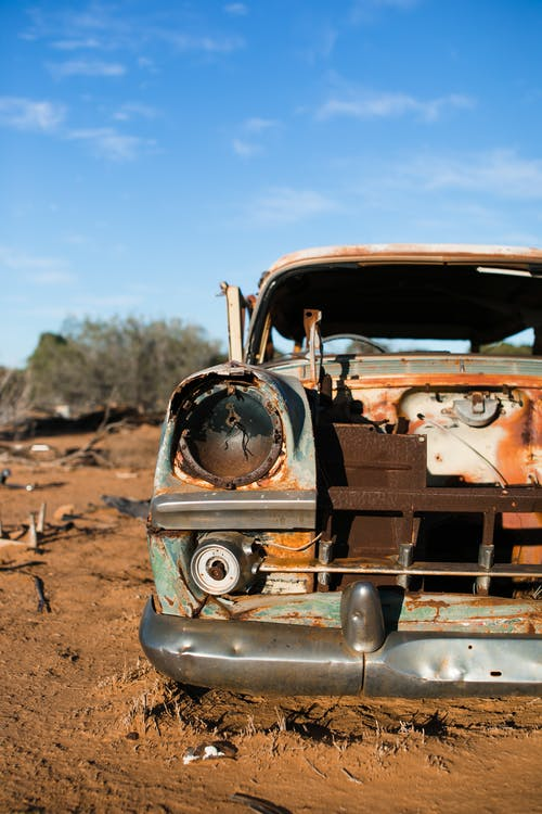 Rusty broken automobile with headlight and damaged bumper placed on sandy land in junkyard against cloudy sky in sunny countryside