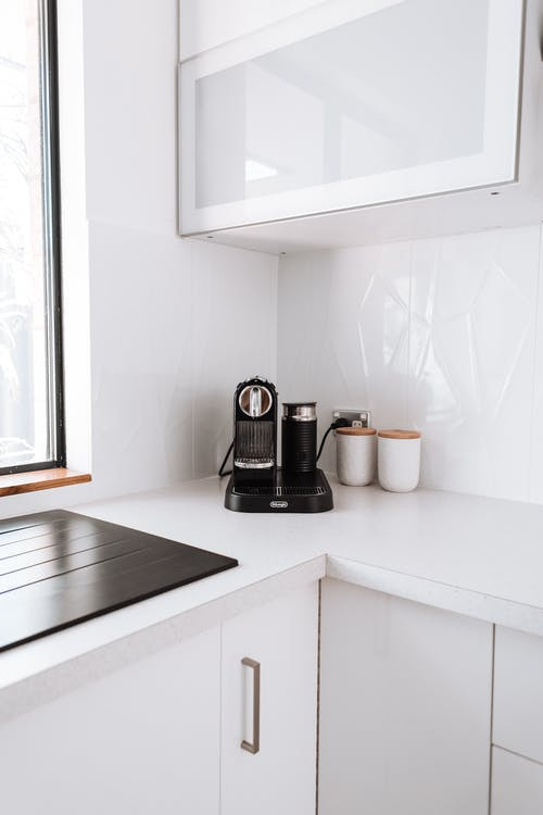 Modern electric coffee maker placed on white counter in kitchen near black stove and cupboards in light apartment with window