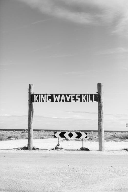 Black and white of king waves kill sign warning of danger of sea storm located near road