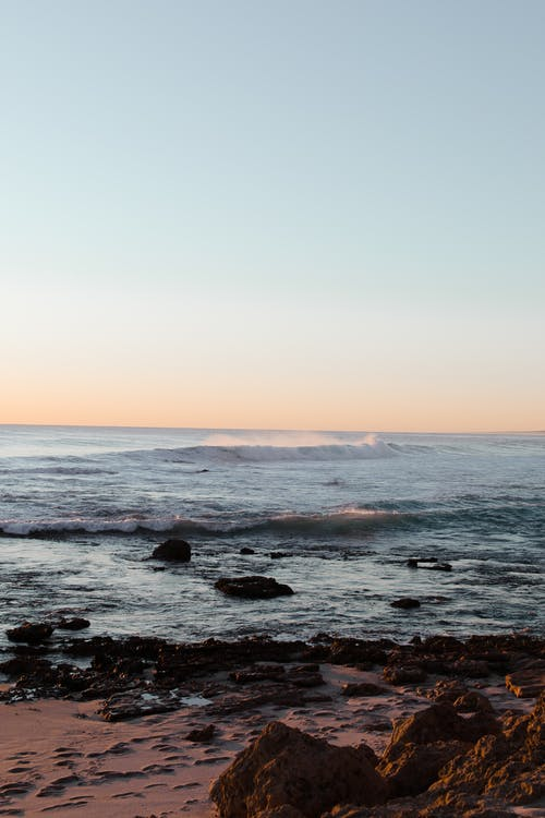 Waving sea washing sandy shore and rocks