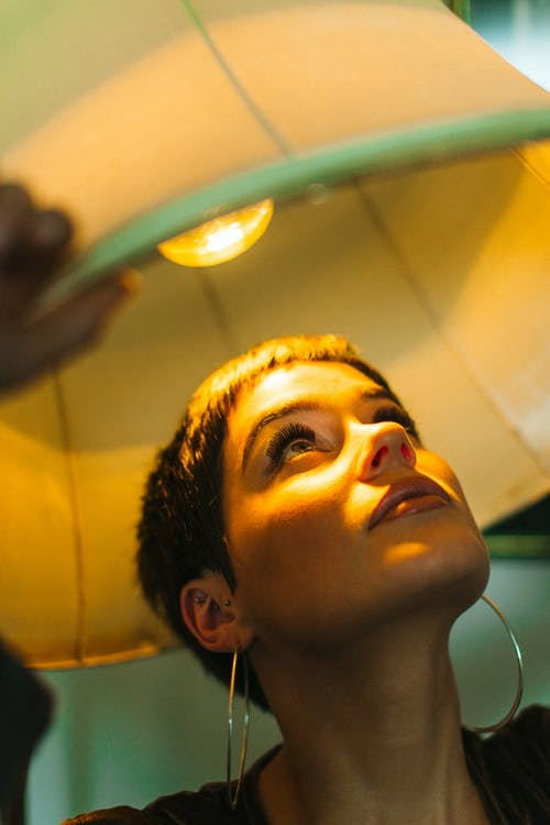 Stylish female with makeup wearing earrings under lamp with shining light bulb looking up