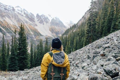 Traveler standing on stones in mountainous terrain