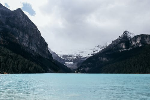 Calm rippling blue lake surrounded by mountains and forest