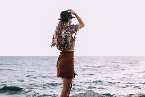 Back view of anonymous female with hand on head in stylish outfit standing on coast and admiring rippling sea