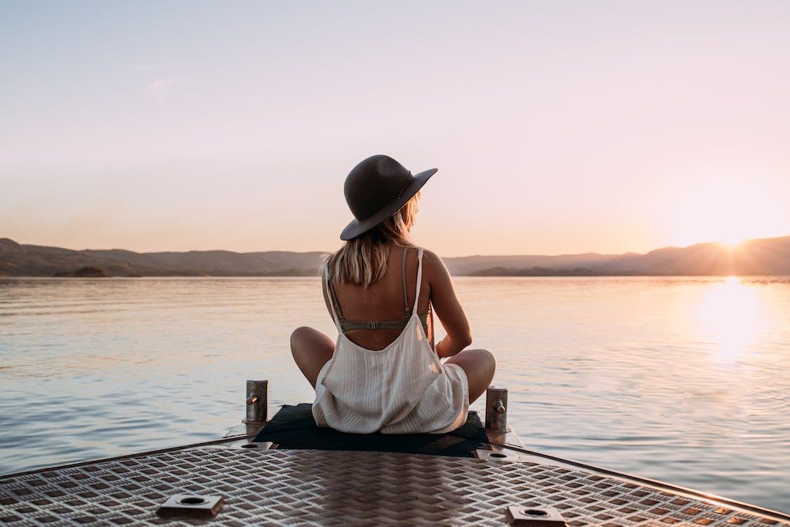 Woman in hat enjoying sunset on pier