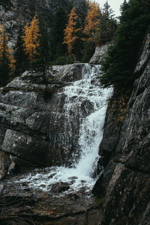 Waterfall flowing through mountains in autumn day