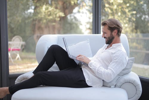Woman in White Long Sleeve Shirt and Black Pants Sitting on White Couch While Reading Book