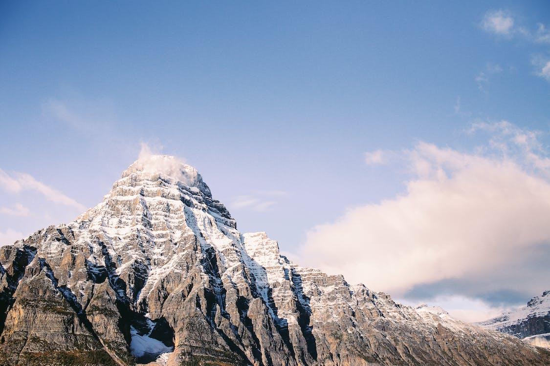 Snowy ridge in mountainous terrain under cloudy sky