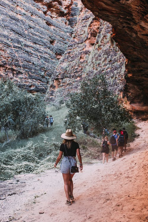 Travelers walking on sandy ground through steep stony mountains while exploring nature during trip