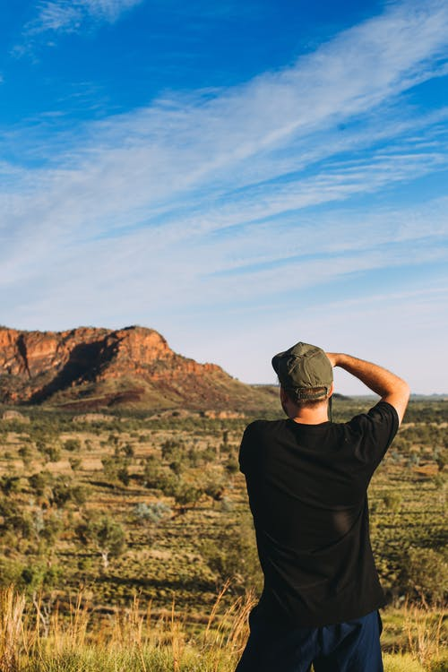 Unrecognizable man taking photo of nature in dry terrain