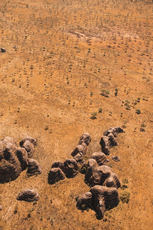 From above of stony formations located on dry sandy area with green rare vegetation in wild nature on drought terrain