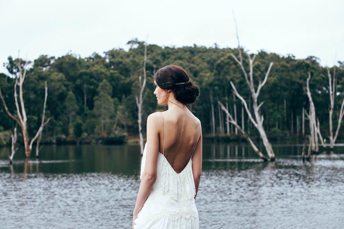 Anonymous elegant bride standing near lake