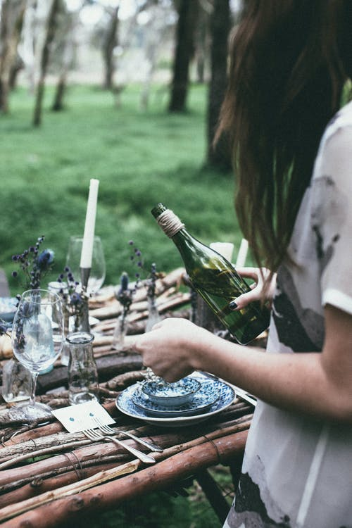 Crop woman pouring wine at table in nature