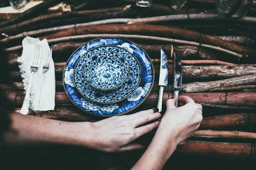Crop woman serving cutlery on table