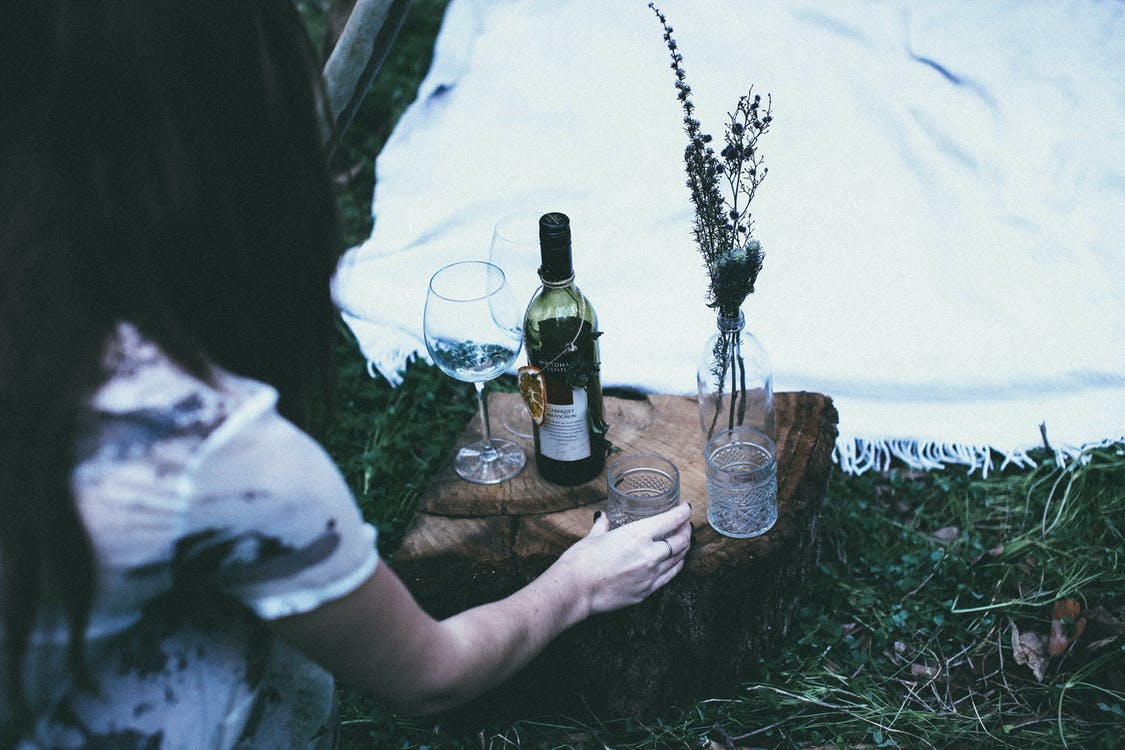 From above of unrecognizable female wineglasses and bottle of alcohol drink on grassy ground with blanket during picnic in nature