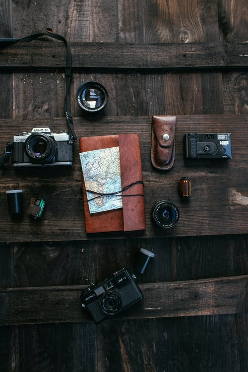 Top view collection of old fashioned photo cameras with lenses and films placed on wooden surface with notepad and map