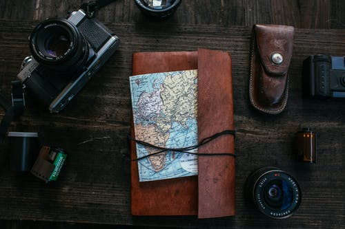 Top view of notebook with map for traveling placed on wooden surface near retro photo camera with film and lens near knife case
