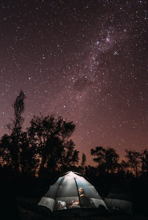 Anonymous camper in tent against starry sky