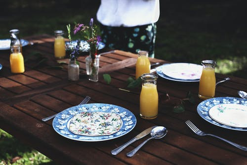 High angle of crop anonymous person standing in green lawn near wooden table with served plates and natural juices on sunny day