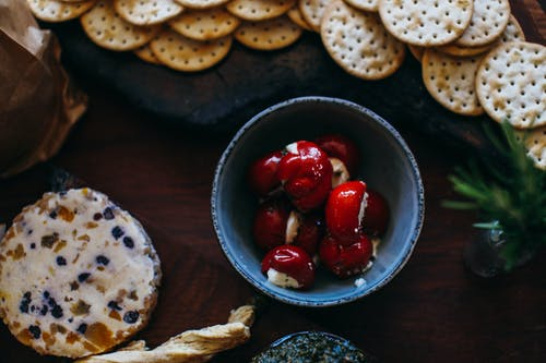 Top view bowl with red tiny cherry peppers stuffed with ricotta placed near salty crackers and assorted cheese