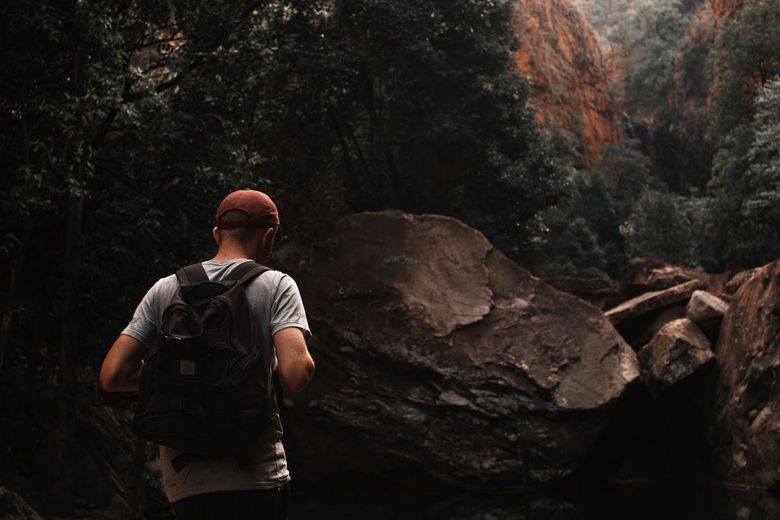 Anonymous male backpacker exploring rocky mountains during hiking trip