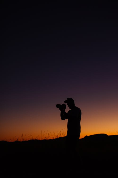 Side view silhouette of anonymous male traveler taking photo of nature standing on grassy meadow against cloudless colorful sunset sky